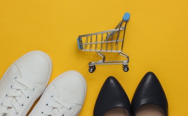 Family shopping leather high heel shoes  white sneakers shopping trolley on yellow pastel background