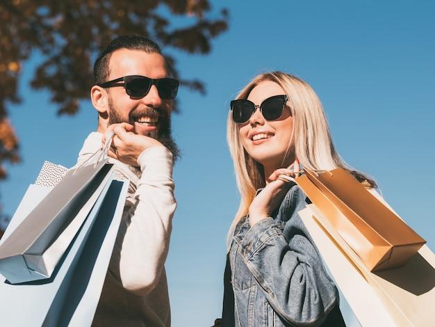 Family shopping leisure couple holding packages, enjoying sunny day, smiling