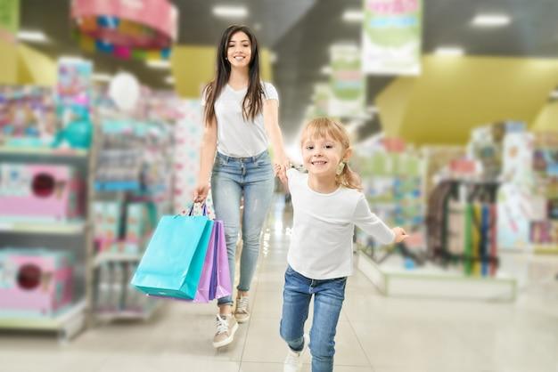 家族の買い物。ショッピングモールを歩く母と子。