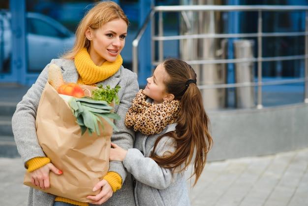 家族で買い物。母と娘は野菜の入った食料品の買い物袋を持っています。