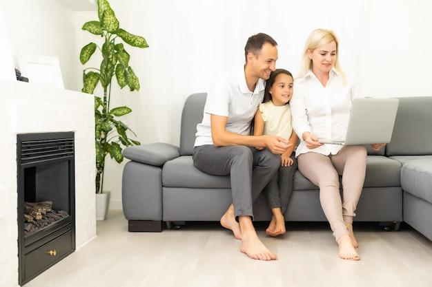 家族のオンラインショッピング。ソファに座って一緒にオンラインショッピングしながら笑顔の幸せな家族