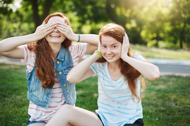 Family shot of two beautiful redhead girls with freckles fooling around while sitting on grass in park during picnic with best friends, covering eyes and ears, being childish, relaxed and carefree.