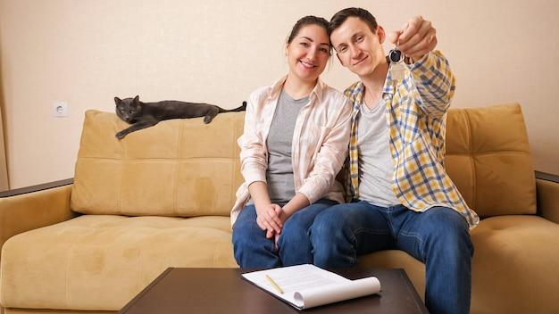 Семья показывает ключи, сидя с милой кошкой на диване в комнате