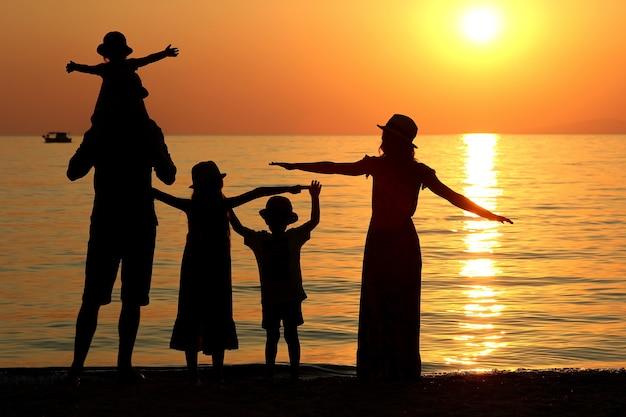 여름에 바다에서 일몰에 가족 실루엣