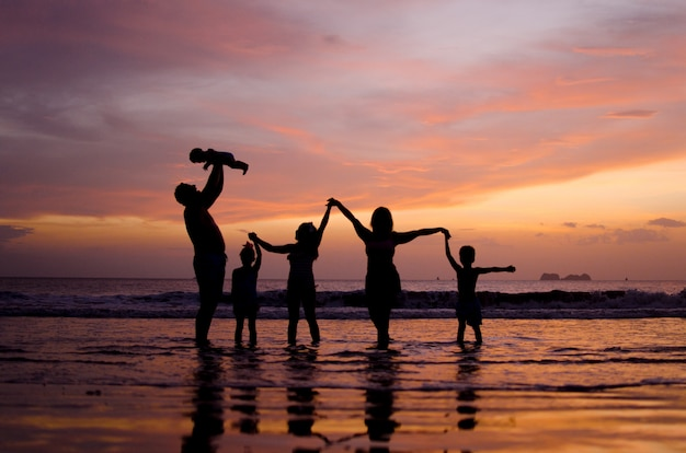 Family silhouette at the sunset beach.