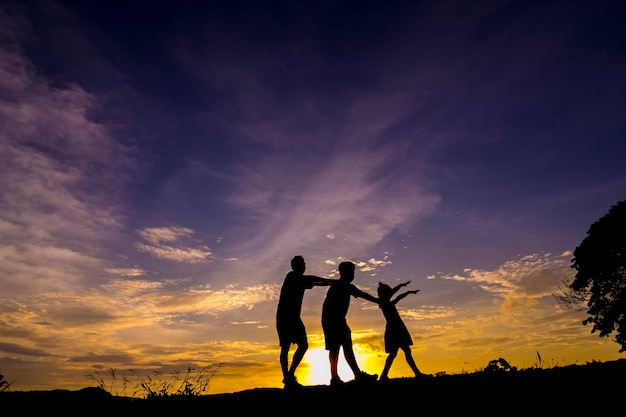 A family silhouettes playing at sunset