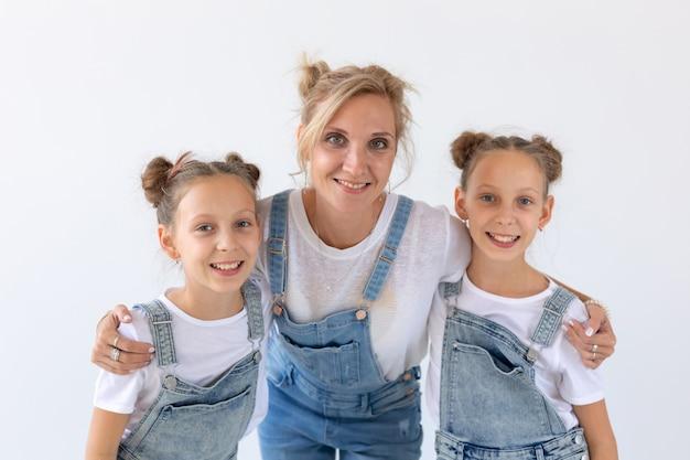 Семья, сестры и концепция любви - мать обнимает двух дочерей-близнецов над белой поверхностью.
