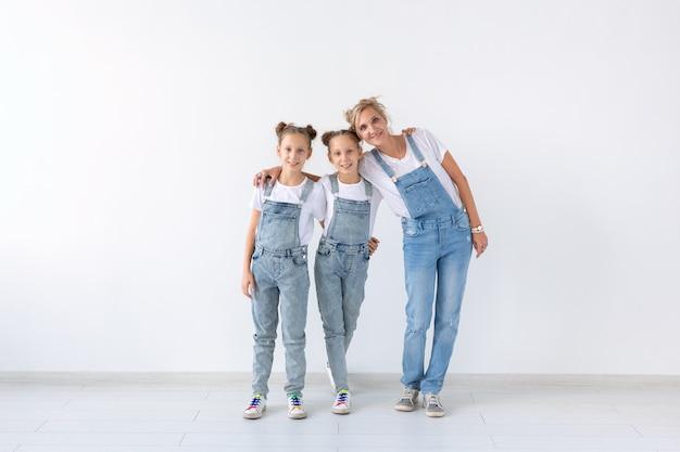 Концепция семьи, сестер и любви - мать обнимает двух дочерей-близнецов над белой стеной с копией пространства