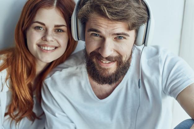 Семья сидит у окна в наушниках технология романтика радость