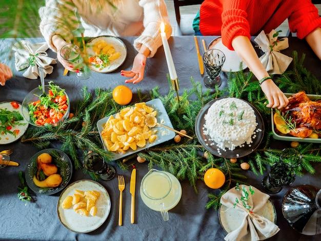 食物でいっぱいのクリスマステーブルに家族が座っています。