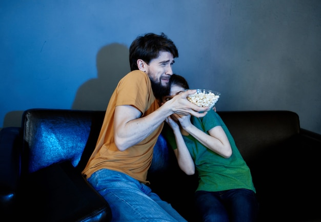 Family sitting on the couch in the evening watching tv with popcorn entertainment