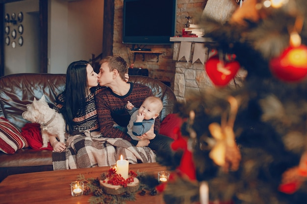 Family sitting on couch with christmas tree out of focus in front