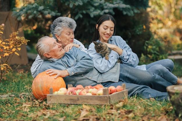 Famiglia che si siede in un giardino con le mele e la zucca