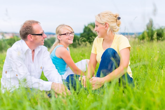 Family sitting on grass of lawn or field