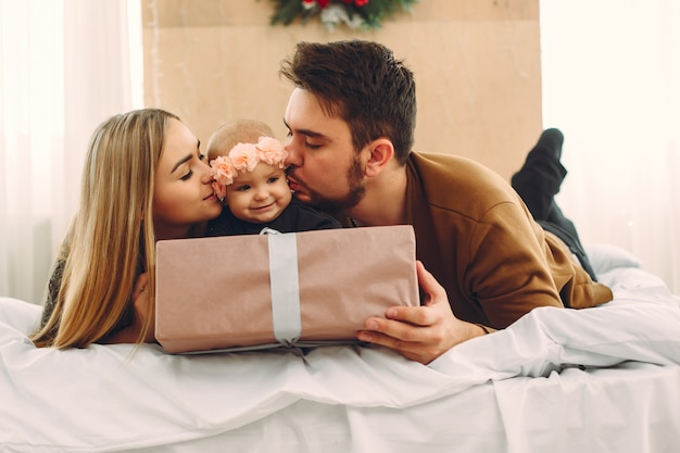 Family sitting at home on a bed with presents