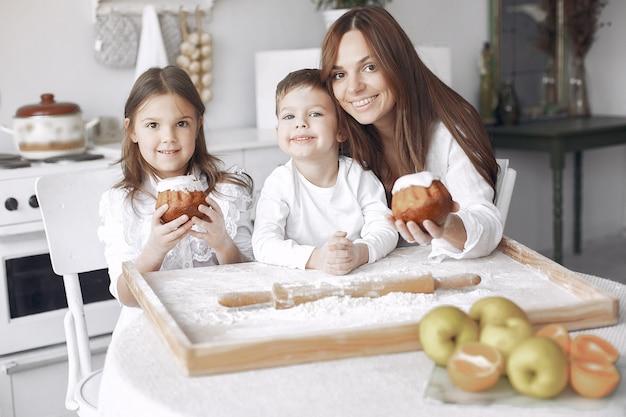 家族は台所に座ってケーキの生地を調理します