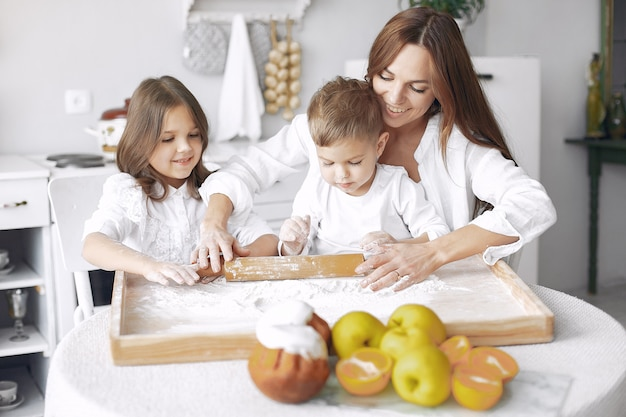Family sitting in a kitchen and cook the dough for cake