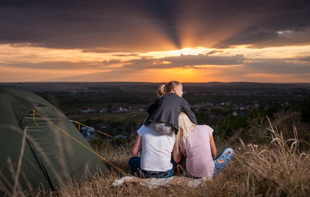 Family sitting near camp tent on the hill