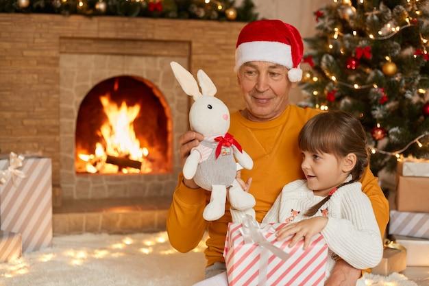 クリスマスツリーと床の暖炉の近くに座っている家族、小さな女の子と祖父