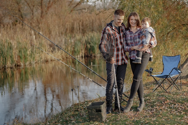 Family sitting near river in a fishing morning