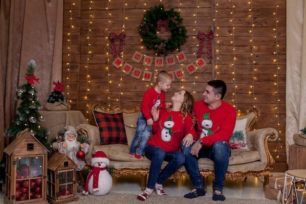 Семья, сидя на диване у себя дома возле елки