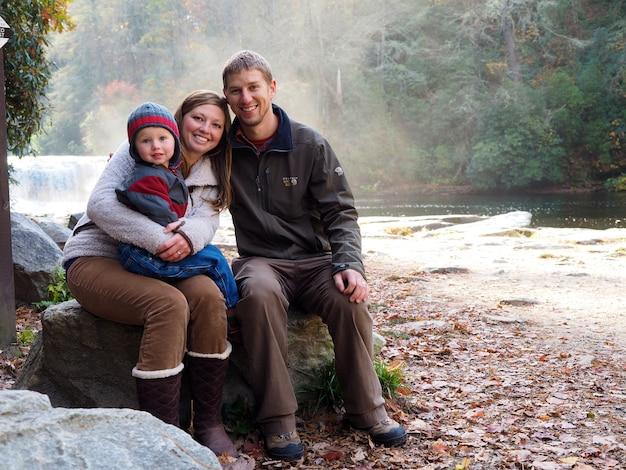 滝と日光の下で緑に囲まれた岩の上に座っている家族