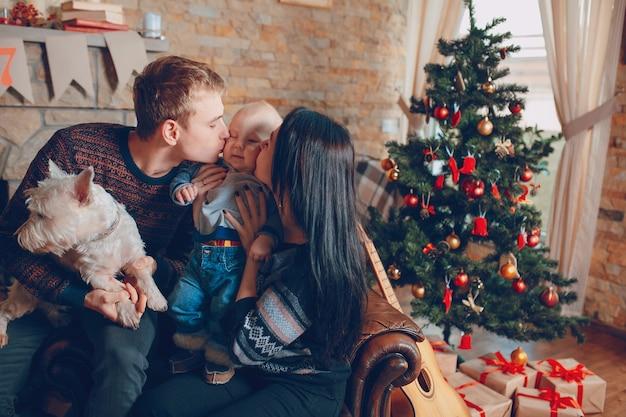 Семья, сидя на диване с собакой на рождество