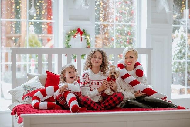 クリスマスの日にベッドに座っている家族