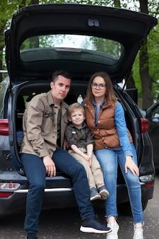車の開いたトランクの端に座っている家族