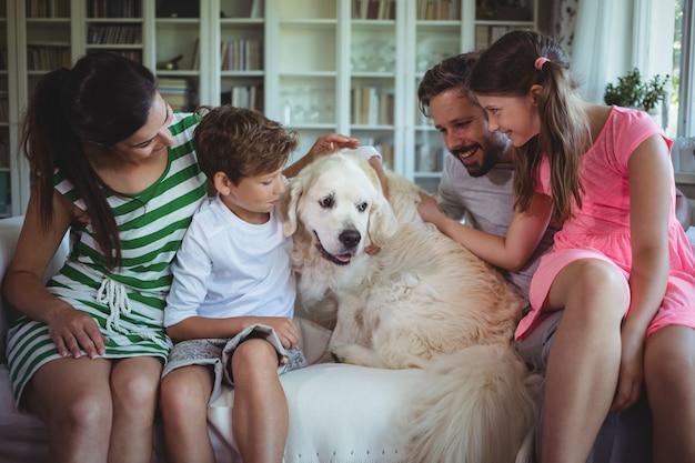 家族のリビングルームでペットの犬とソファに座って