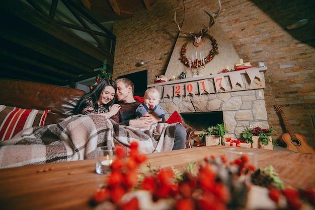 Семья, сидя на диване, облеченная одеялом и видно из рождественских украшений деревянный стол