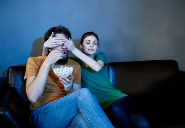 Семья сидит на диване вечером и смотрит телевизор с попкорном
