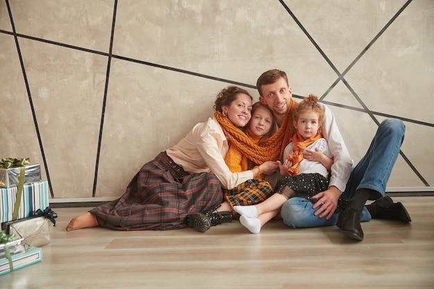 Семья сидит на полу в новой квартире