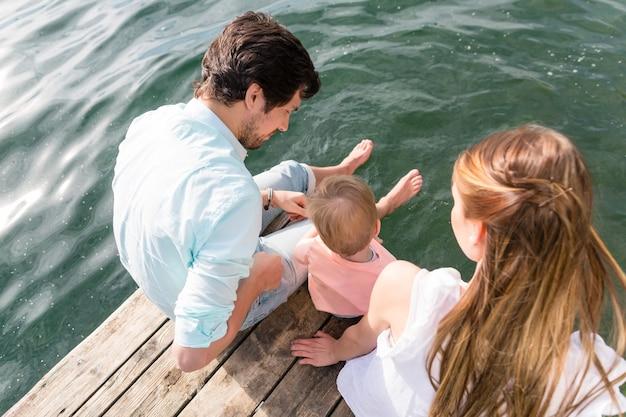 Семья сидит на воде, свешивая ноги в пруду, вид сверху