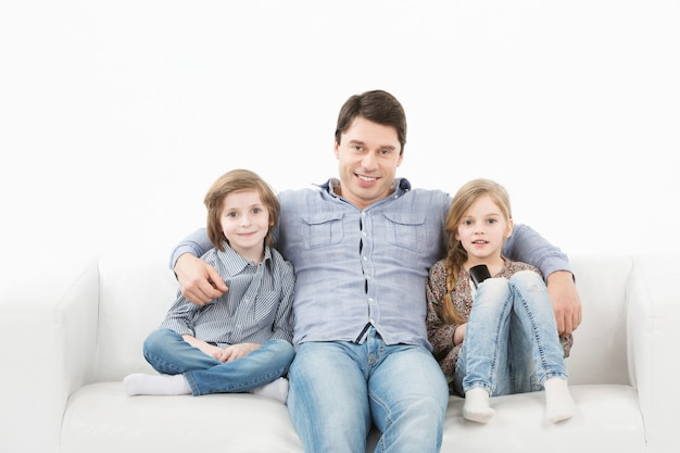 Family sitting on sofa smiling at camera on white wall