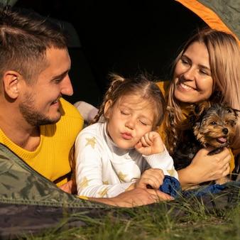 Famiglia che si siede in tenda con il loro primo piano del cane