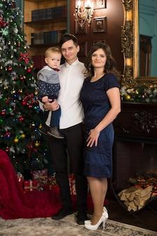 クリスマスのインテリアに一緒に座っている家族。幸せな家族はクリスマスプレゼントを楽しんでいます。クリスマスの家族の肖像画、母、父と息子はその機会を祝います。