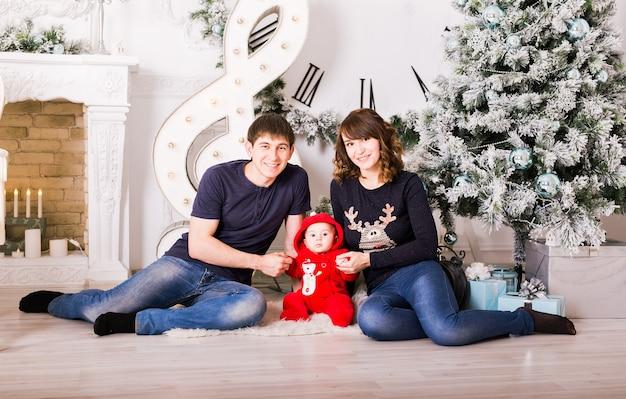 Семья, сидя под рождественской елкой., мать отца и ребенка ребенка в украшенной комнате
