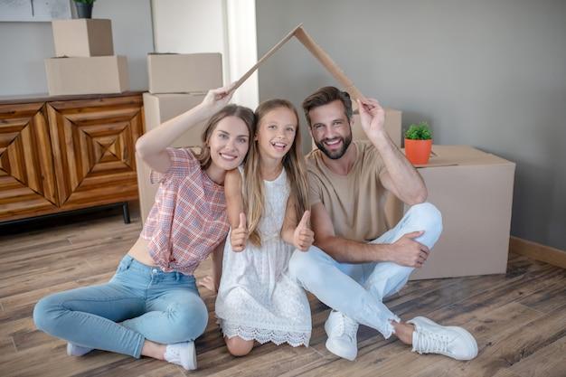 紙の屋根の下に座って、笑顔の家族