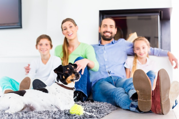 Family sitting with dog at living room floor fireplace