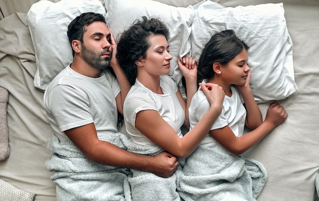 The family sleeping in the comfortable bed.