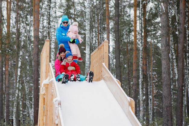 Семья спускается с ледяного деревянного холма в снежный день. отец, мать, сын и дочь эмоционально смеются и радуются зиме на природе. яркая одежда, высокая гора, сосновый бор.