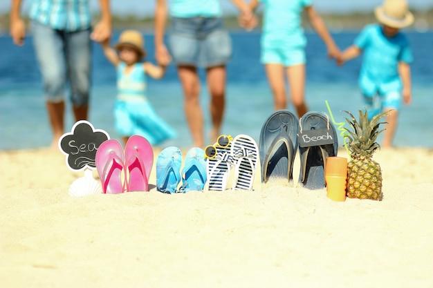 夏のビーチの砂の上の家族のスリッパ