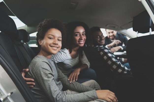 Family smiling sitting in a car