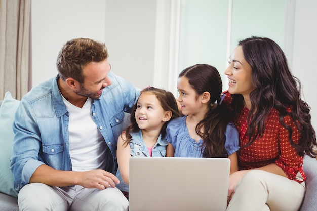 Family smiling and using laptop on sofa