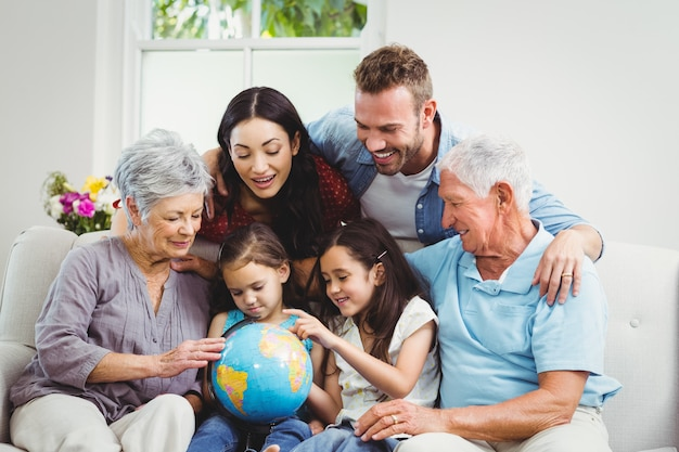 Family on sofa looking at earth globe