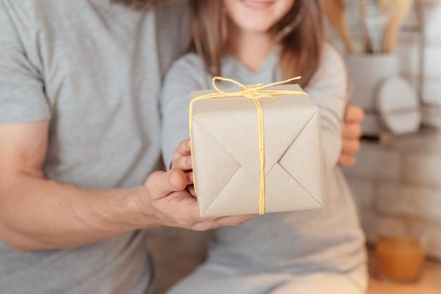 家族の特別な日。ラップされたギフトを一緒に持って、誕生日の女の子を抱き締める愛情のある父のクロップドショット。