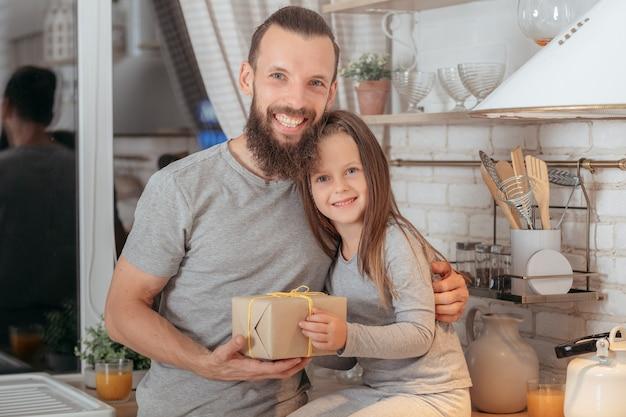 Семейный особый случай. любящий отец с его милой маленькой дочерью держит подарок, обнимает, улыбается.
