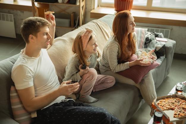 家族は家で一緒に素敵な時間を過ごし、幸せで陽気に見え、ピザを食べています