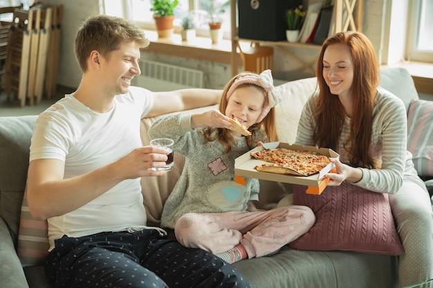 Семья, проводящая время вместе дома, выглядит счастливой и веселой, ест пиццу